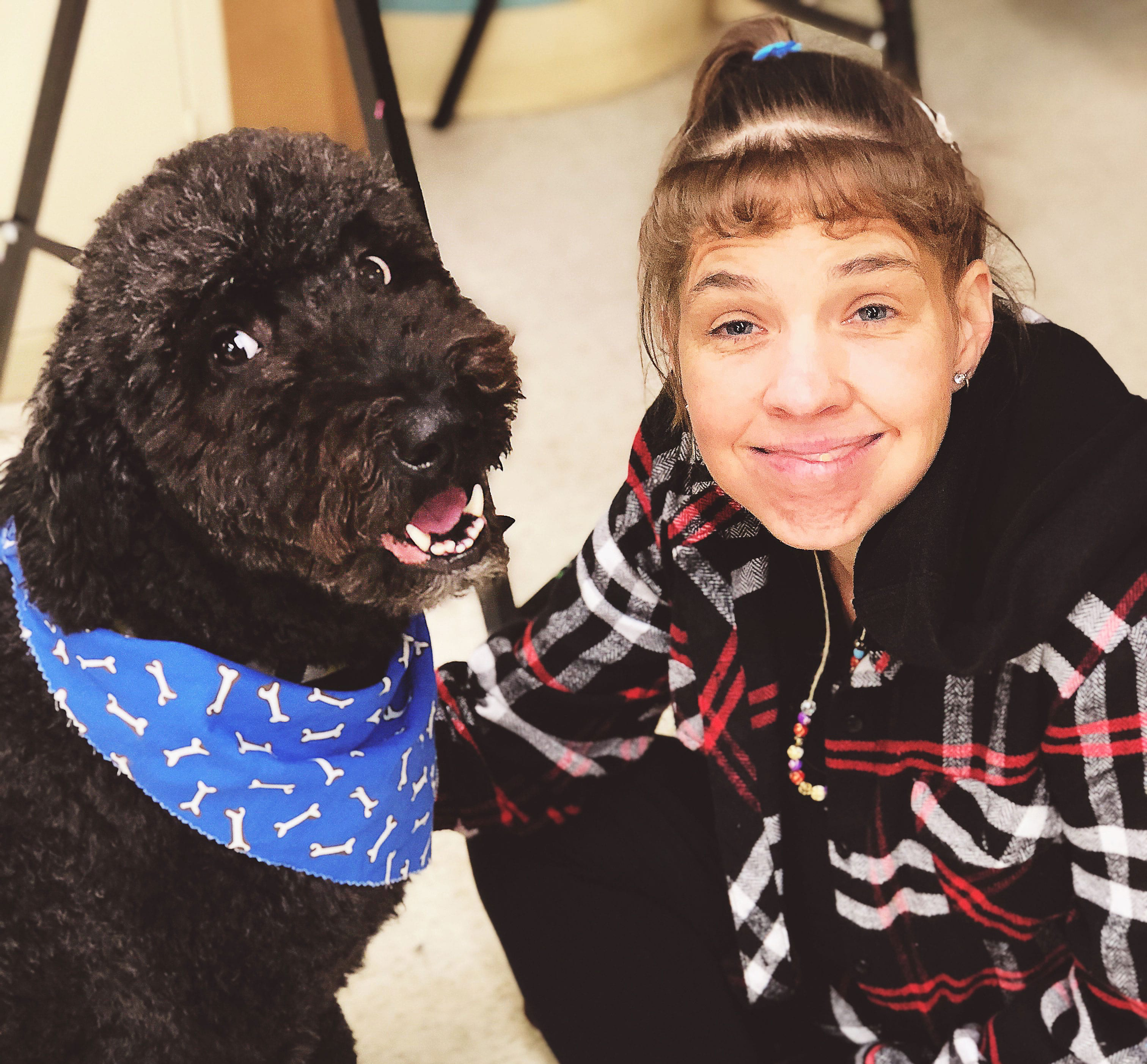Female client smiling is kneeling down and face to face petting a happy and gentle looking black dog with a blue bandana that is part of the pet therapy program.