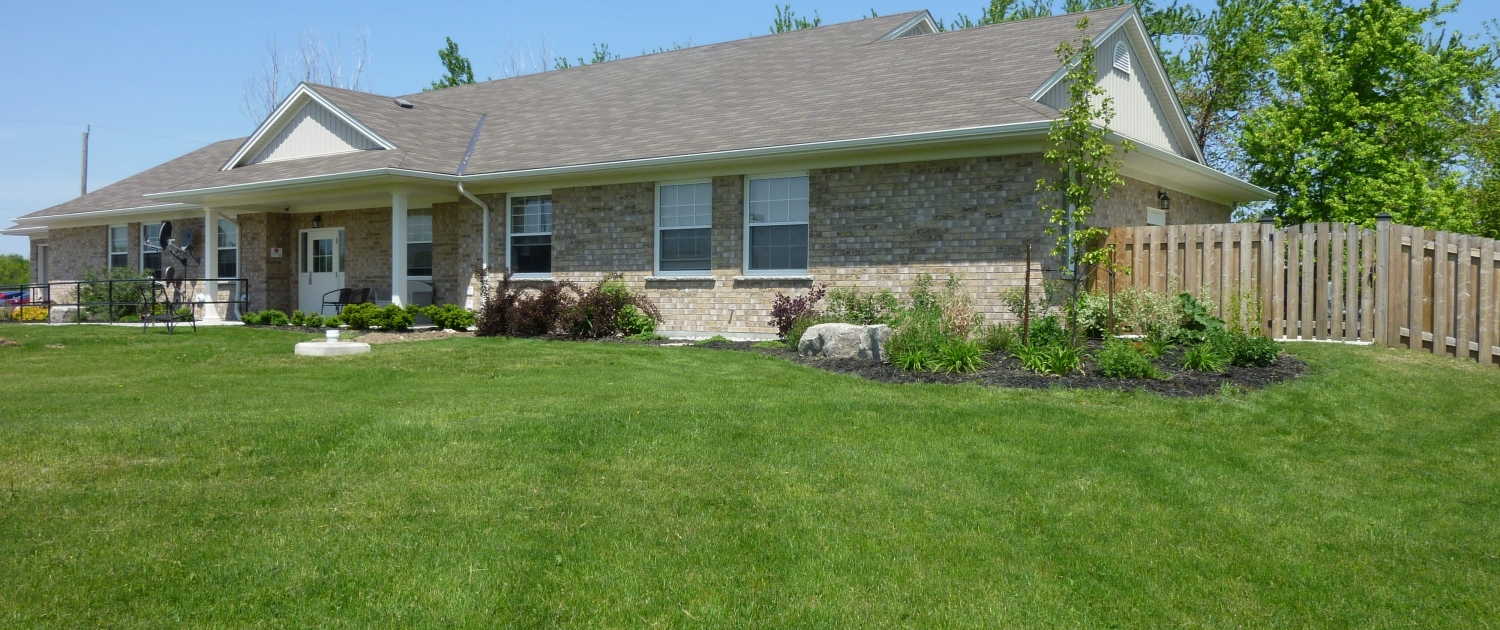 Large beige brick ranch-style bungalow has lots of front windows a covered entrance and a fenced area on the right side. It is surrounded by a well maintained lush green lawn and landscaped with trees and shrubs.