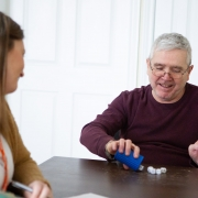 Male client empties out his cup of yahtzee dice onto the table while female staff looks on. They both are smiling.