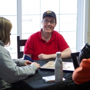 Male client smiles candidly at the camera while playing scrabble at a table with female staff.