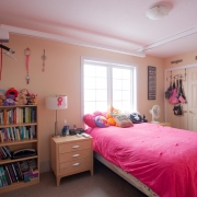 Client's bedroom has bookshelf filled with various books and stuffed animals on top; a beige night stand with a lamp, personal products and radio on top; a single bed underneath a window with a bright pink duvet with pillows and stuffed animals on top of the covers; double closet doors on right side of the room; a hoyer lift and belt attached to the ceiling for transfer support.