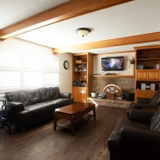 Country style living room has dark wood floors and wood beams on the white ceiling. The wall mounted tv unit is above a brick hearth and flanked by medium brown wooden built-in shelving units. 2 large couches and a coffee table furnish the room.