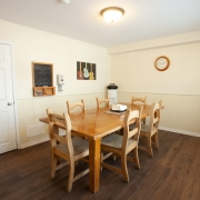 Dining area with wooden dining table and 6 chairs. Wall hangings and a clock displayed on the beige walls.