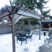 Outdoor black metal patio table and chairs sit under a wooden trellis structure in a fenced in back yard with a large evergreen tree in the background behind the fence. The ground is snow covered.