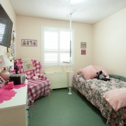 This client's bedroom has a White dressor with pink accents including lamp, radio and picture frames on the left side of the room; TV mounted above; Pink plaid lazy boy chair in top corner; single bed with pink pillows and floral duvet along the right side of the room with assist lift pole.