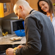 Male is smiling while preparing food at the stove, while female watches and smiles.