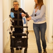 Female client using a walker is assisted by a female staff member while they walk together down a hall.