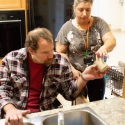 Male patient in a wheel chair sitting in front of a sink and female staff standing beside him are in the kitchen working together to put dishes in the dishwasher.