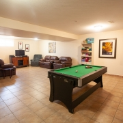 Large open and bright windowed basement room. There is a pool table set up at one end with lots of space around it. 2 brown couches and 2 lazy boy chairs are set up against the wall close to a brown tv stand and television at the other end. A shelving unit near the pool table is stocked with various items and there is a colourful painting hanging on the wall behind the pool table. 3 pictures are hanging in the tv area, one over the couch and 2 on the wall beside the tv.