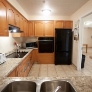 Kitchen with light brown wood cabinetry, black fridge, wall oven, counter cook top and microwave. Double sinks are surrounded by marbled beige countertops.