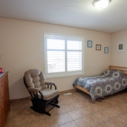Client's bedroom has a white window and beige painted walls. A single bed with a geometric design on the bedspread is situated in the back right hand corner. A brown wooden dresser is against the wall on the left, and a comfy looking beige recliner rocker is set up near the window. 4 small works of art are hanging on the walls by the bed.