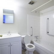 All white bathroom has a white vanity with 2 doors to the left and a mirror hanging above. A white toilet is in the middle and a white bathtub shower unit surronded by white tiles is situated to the right. The bathtub is equipped with 2 safety bar handles, a white curtain rod is attached to the wall, and a fan/vent is installed on the ceiling.
