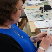 Female client sitting at a table, holding a white mask that says 'STAY STRONG' on the forehead; she is designing the mask as part of a creative expression workshop with the intention of reflecting on her personal brain injury journey.