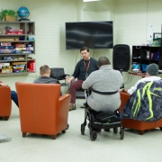 Male resource nurse sits in front of 4 male clients facilitating a presentation on health. 3 clients are sitting in big orange easy chairs, and one is sitting in front of the nurse in a wheelchair.