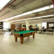 Large, spacious and bright games room. Pool table in the middle of the room has lots of open space around it. A few tables with chairs are set up in the background to accommodate other client activities.
