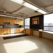 Large and spacious communal full kitchen for Group Services. Open floor space is available in the middle of the room; wooden cabinetry including a diswasher span the back wall. 2 large windows provide a lot of natural light into the space.