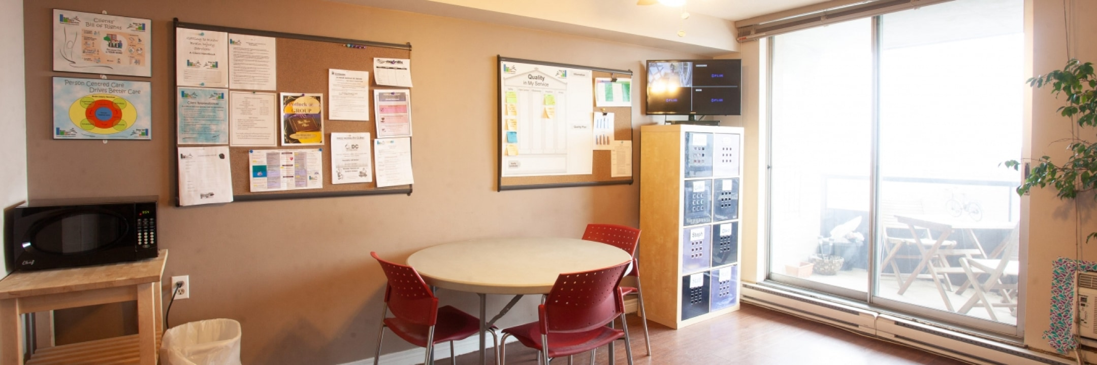 Bright room with beige painted walls has a round table and three red chairs against the wall in the middle. A black microwave sits on a wooden stand on the left hand side, and three bulletin boards with organized notices attached are hung spaced out along the wall. A filing unit has a tv screen sitting on top in the corner of the room near large window sliding doors that lead to an outdoor patio.