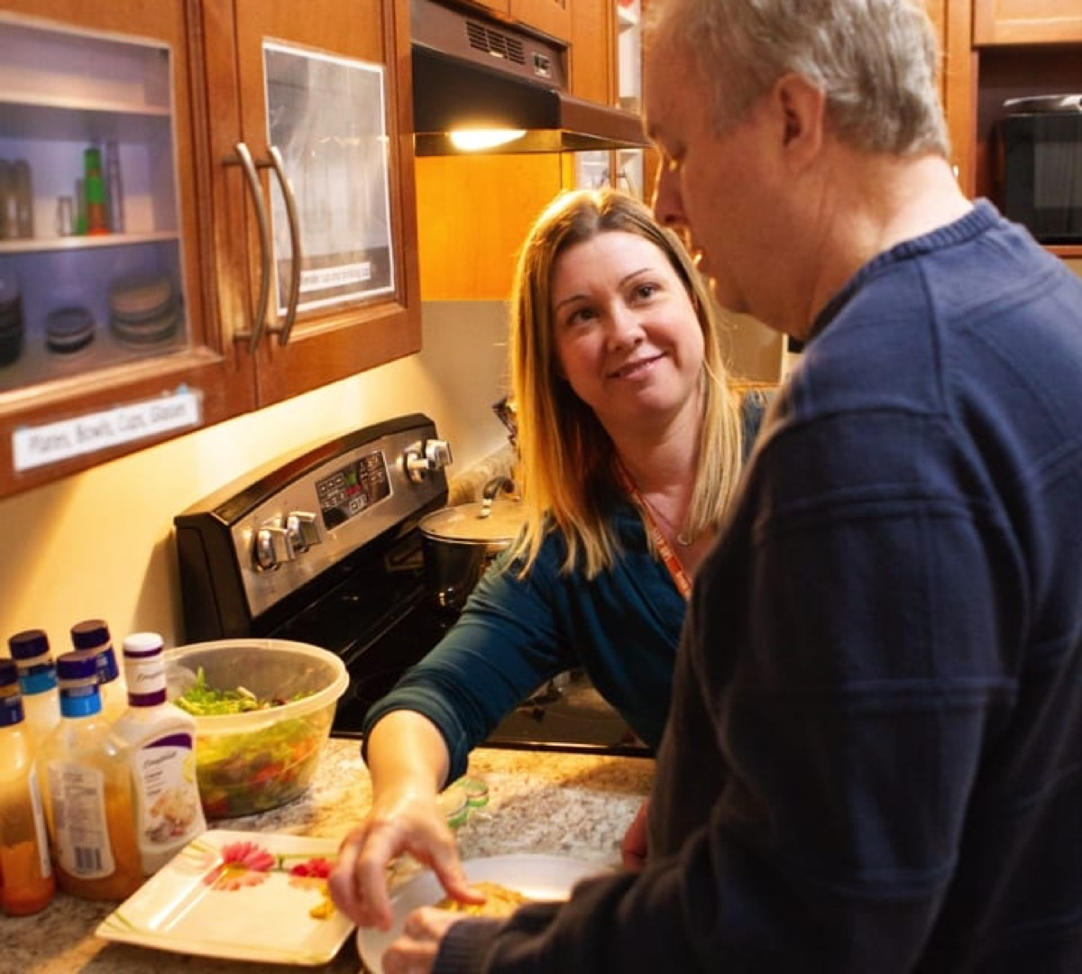 Male client is with smiling female staff member standing together at the kitchen counter preparing plates for a meal.