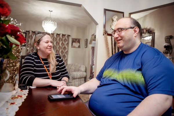 Male client and female staff are smiling at each other while sitting across from each other at a family dining table in a client's home. The male client is working on an electronic device at the table developing his technology skillset.