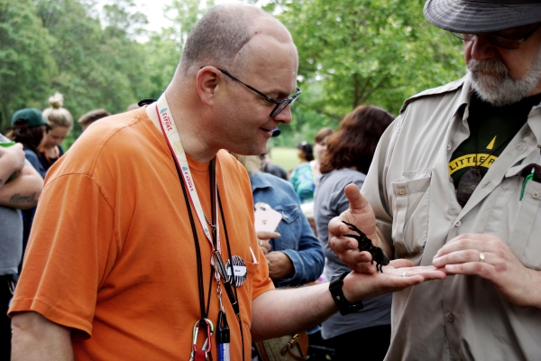 Male client looks on intently while an exotic animal exhibit staff member places a large black spider in his outstreched hand at an exotic animal exhibit at the annual client picnic.
