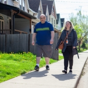 Male client and female staff are walking side by side on a sidewalk in front of a row of townhouses on a sunny day.