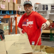 Male client is standing at a table in a large wearhouse. He is holding a cardboard box and packing tape while he works to break down the box. He is working at a food bank during a volunteer placement.