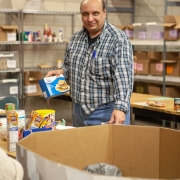 Male client is standing in the middle of a large wearhouse in front of a large open cardboard box. There are several open shelving units along the back that are housed with food and other boxes. The client is holding a box of food in his right hand and looking at the camera. He is organizing food donations at food bank during volunteer placement.