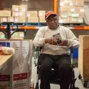 Male client in a wheel chair is sitting in the middle of a wearhouse looking at a brochure. There are several large boxes around him, and orange metal shelving units are lined up against the back. Small labelled boxes in taped together groupings are housed on the shelves behind him.