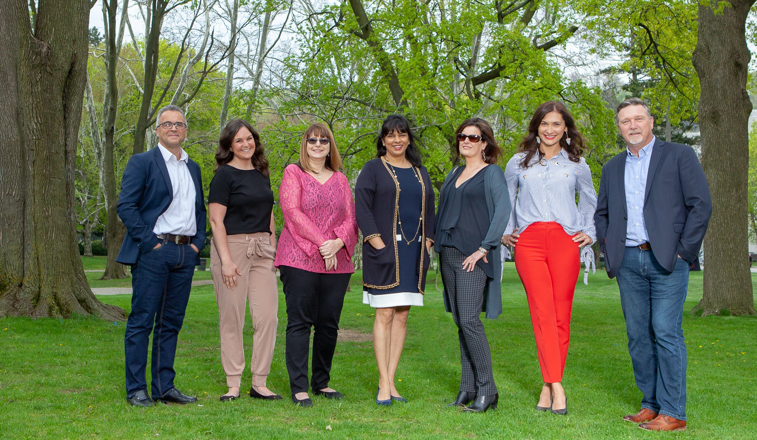 Leadership team from left to right: Vlad Bartchouk, Mary Jackson, Nadina Salciccioli, Mila Ray-Daniels, Candy Sarraf, Joanna Pajak, Steve Dawn. Staff members are standing in a row on lush green grass in a park like setting, surrounded by many large trees.